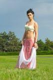 Mujer atractiva que presenta en un parque fotografía de archivo libre de regalías