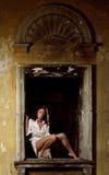 Mujer atractiva que presenta en ventana Fotografía de archivo
