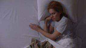 Mujer atractiva que recuerda sus últimas relaciones mentir en cama por la tarde, topview metrajes