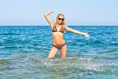 Mujer atractiva que salpica en el mar foto de archivo