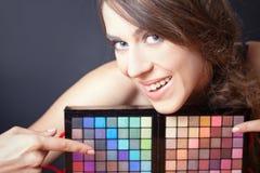 Mujer atractiva que señala en la paleta colorida para el maquillaje de la moda Imágenes de archivo libres de regalías