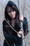 Mujer atractiva que se coloca en el medio de árboles secos Imagen de archivo libre de regalías