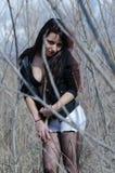 Mujer atractiva que se coloca en el medio de árboles secos Foto de archivo
