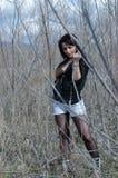 Mujer atractiva que se coloca en el medio de árboles secos Fotografía de archivo