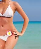 Mujer atractiva que se coloca en la playa Foto de archivo libre de regalías