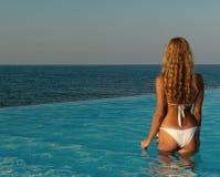 Mujer atractiva que se coloca en piscina del infinito Imagen de archivo