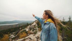 Mujer atractiva que se coloca en un pico de montaña con su pelo largo que sopla en el viento que sonríe y que intenta guardar su  almacen de metraje de vídeo