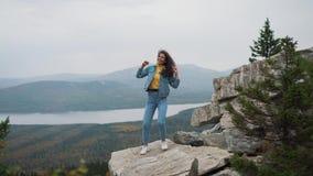 Mujer atractiva que se coloca en un pico de montaña con su pelo largo que sopla en el viento que sonríe y que intenta guardar su  metrajes