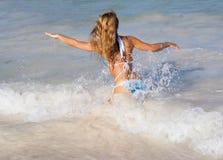 Mujer atractiva que se ejecuta en ondas en la playa del Caribe Foto de archivo