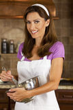 Mujer atractiva que se mezcla y que cuece al horno en cocina Fotos de archivo libres de regalías