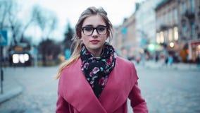 Mujer atractiva que se mueve a la derecha hacia la cámara, mirando alrededor, tocando sus vidrios Mirada de moda Ambientes urbano almacen de video