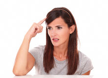 Mujer atractiva que se pregunta con su mano en la cabeza Foto de archivo