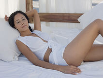 Mujer atractiva que se relaja en cama de la cama imperial Imágenes de archivo libres de regalías