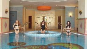 Mujer atractiva que se relaja en piscina interior del balneario en el hotel almacen de metraje de vídeo