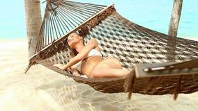 Mujer atractiva que se relaja en una hamaca