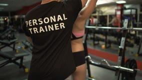 Mujer atractiva que se resuelve con el instructor personal, barra de elevación en gimnasio almacen de metraje de vídeo