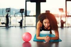 Mujer atractiva que se resuelve con los músculos abdominales en el gimnasio Imagen de archivo