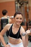 Mujer atractiva que se resuelve con pesas de gimnasia Imagen de archivo