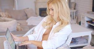 Mujer atractiva que se sienta con el ordenador portátil que muestra hendidura fotos de archivo
