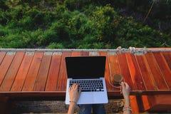 Mujer atractiva que se sienta con un ordenador portátil y una taza de café Fotos de archivo