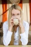 Mujer atractiva que se sienta en café Imagenes de archivo