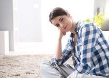 Mujer atractiva que se sienta en el piso Imágenes de archivo libres de regalías