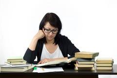 Mujer atractiva que se sienta en estudiar de la tabla Fotografía de archivo libre de regalías
