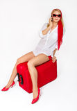 Mujer atractiva que se sienta en la maleta de las vacaciones Fotos de archivo libres de regalías
