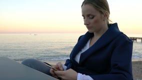 Mujer atractiva que se sienta en la tabla en el café de la playa que envía el mensaje en móvil almacen de video