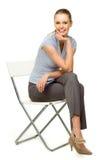 Mujer atractiva que se sienta en silla Imagen de archivo libre de regalías