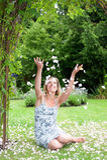 Mujer atractiva que se sienta en un jardín del verano Imagen de archivo libre de regalías