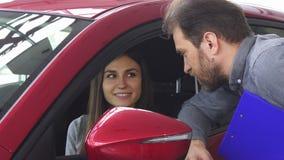 Mujer atractiva que se sienta en un nuevo coche que habla con el vendedor almacen de video