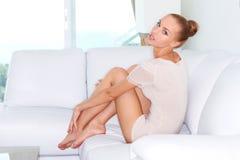 Mujer atractiva que se sienta en un sofá blanco Imagen de archivo