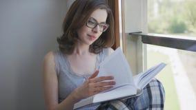 Mujer atractiva que se sienta la ventana y leyendo almacen de video