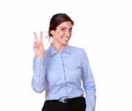 Mujer atractiva que sonríe con la muestra de la victoria Fotografía de archivo libre de regalías
