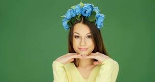 Mujer atractiva que sonríe y que presenta en un tocado floral almacen de video