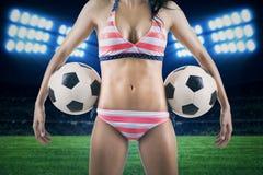 Mujer atractiva que sostiene balones de fútbol en el campo Imágenes de archivo libres de regalías