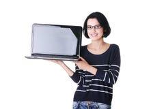 Mujer atractiva que sostiene un ordenador portátil. Foto de archivo