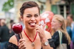 Mujer atractiva que sostiene una manzana caramelizada roja Imagen de archivo libre de regalías