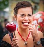 Mujer atractiva que sostiene una manzana caramelizada roja en el Oktoberfest Imagen de archivo