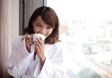 Mujer atractiva que sostiene una taza de café, sonriendo Fotos de archivo libres de regalías
