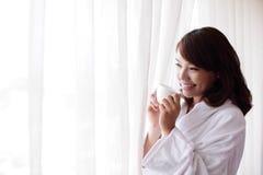 Mujer atractiva que sostiene una taza de café, sonriendo Foto de archivo