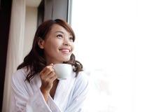 Mujer atractiva que sostiene una taza de café, sonriendo Fotografía de archivo libre de regalías