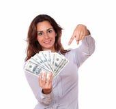 Mujer atractiva que sostiene y que señala el dinero Foto de archivo