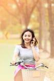 Mujer atractiva que toma con el teléfono mientras que bicicleta del paseo fotografía de archivo libre de regalías