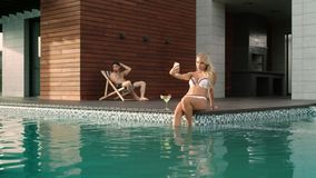 Mujer atractiva que toma el selfie en piscina de lujo Pares felices que se relajan cerca de piscina almacen de video