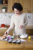 Mujer atractiva que toma un huevo para hacer una receta de las magdalenas Imagenes de archivo
