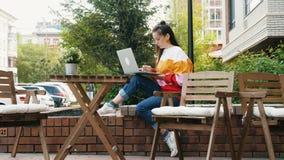 Mujer atractiva que trabaja con el ordenador portátil al aire libre almacen de metraje de vídeo