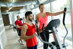 Mujer atractiva que trabaja ejercicios cardiios con el instructor Imagen de archivo libre de regalías