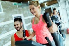Mujer atractiva que trabaja ejercicios cardiios con el instructor Foto de archivo